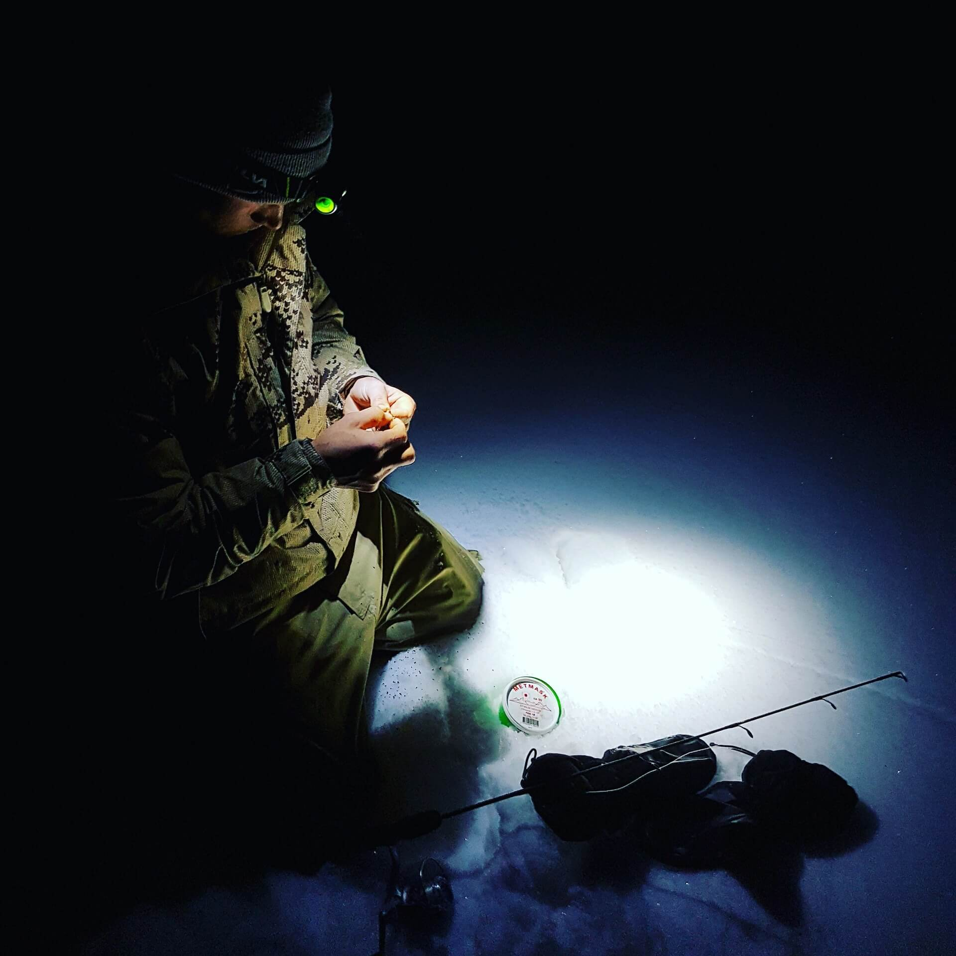 Person wearing best headlamp for fishing at night preparing to Ice Fish