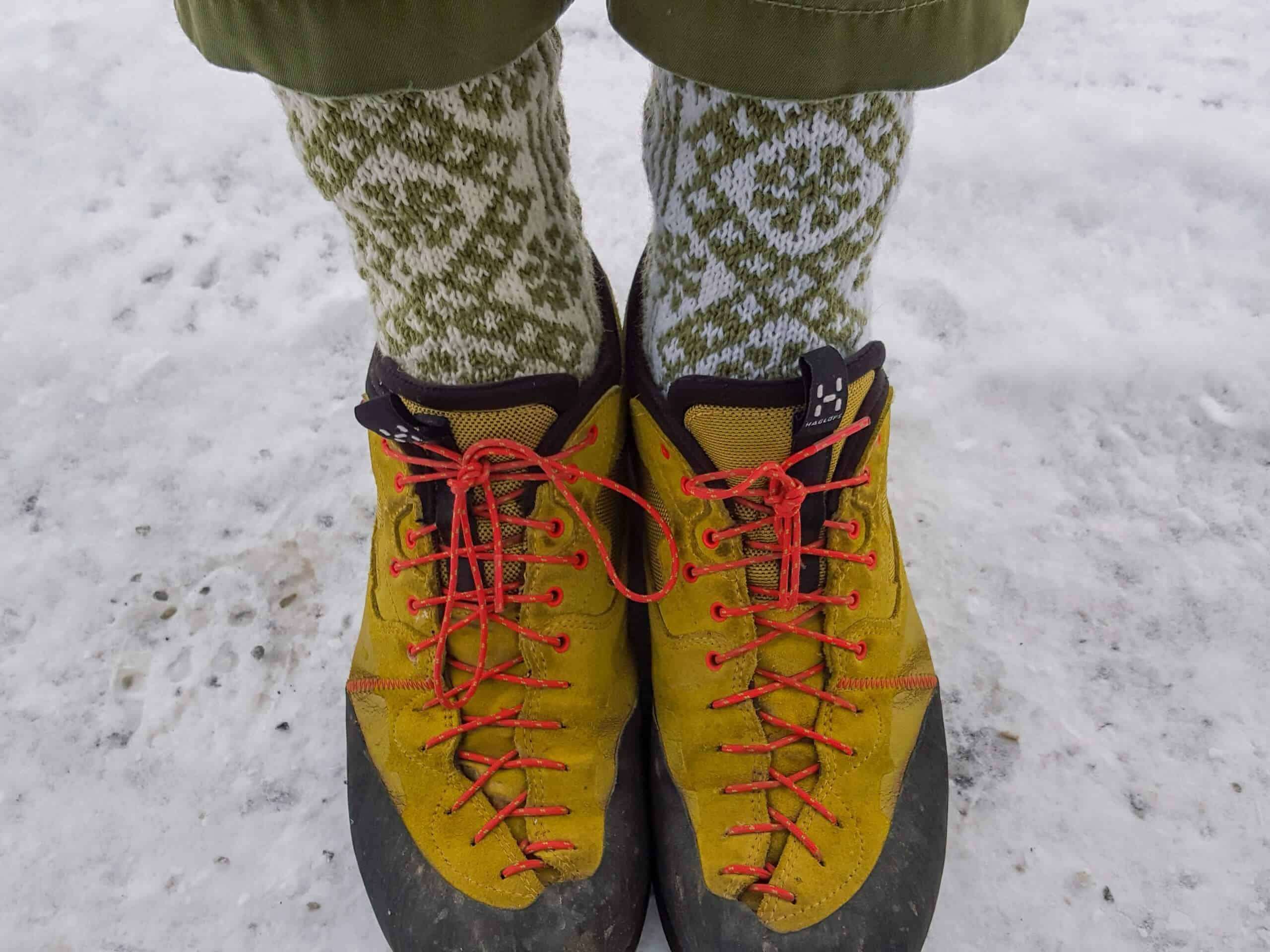 Woman wearing some of the best socks for ice fishing standing on frozen lake wearing winter boots