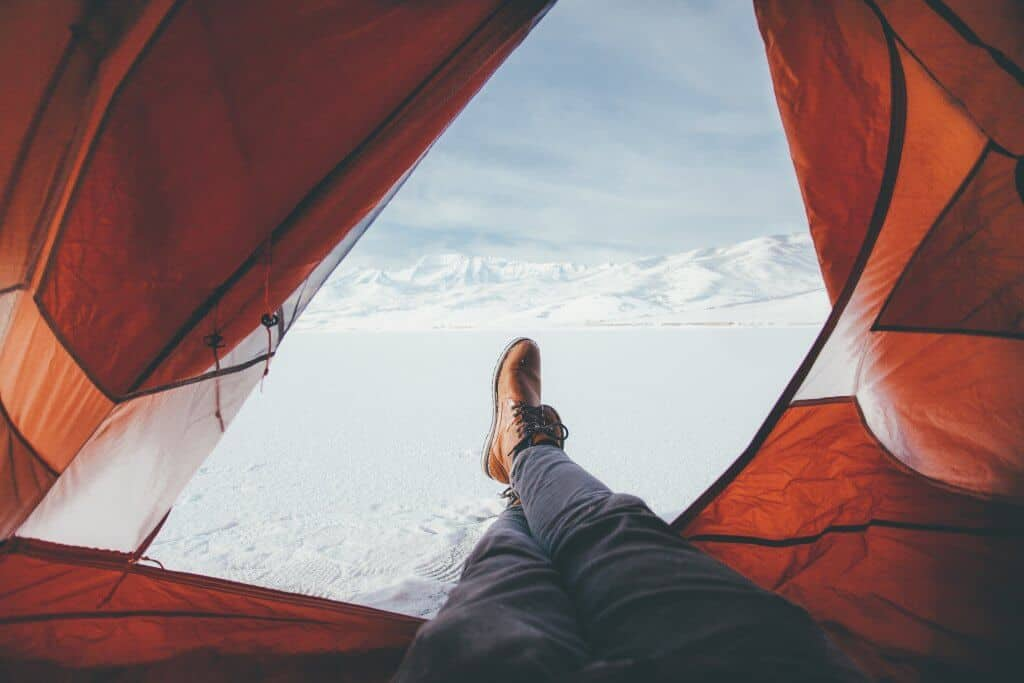 Person relaxing in an open tent on a frozen lake