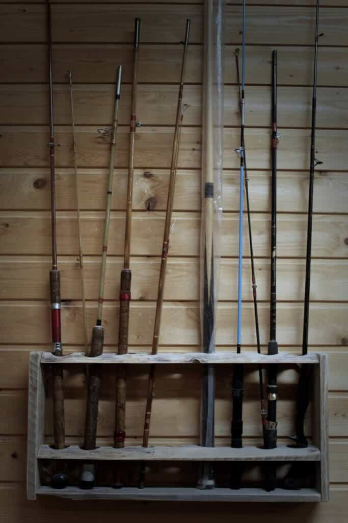 Fishing Rods standing in a rod holder at a wall