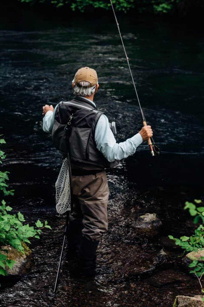 Man angling wearing best fly fishing vest
