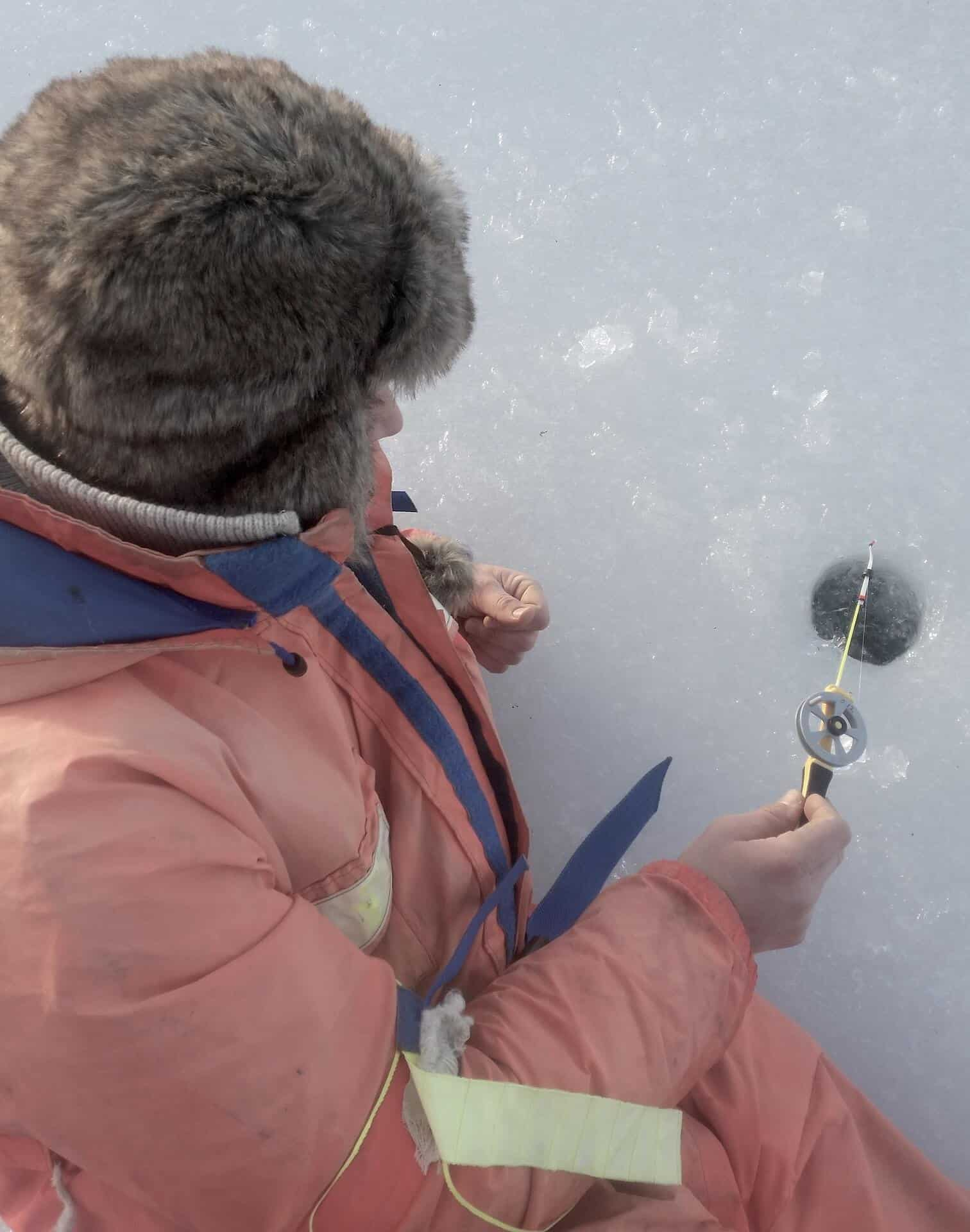 Person ice fishing on a frozen lake holding a rod with one of the best ice fishing reel
