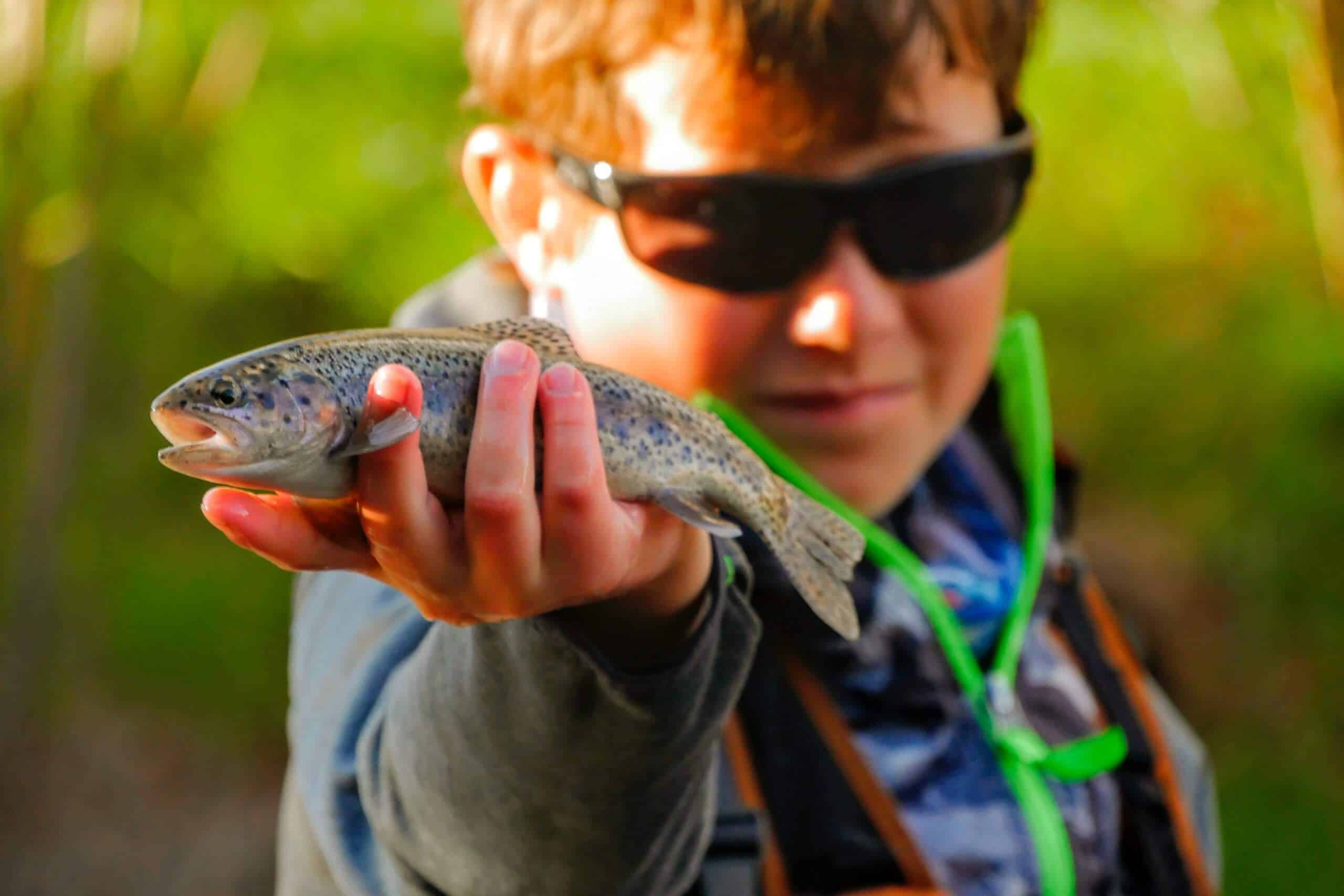 Boy holding fish wearing some of the best fishing sunglasses under $50