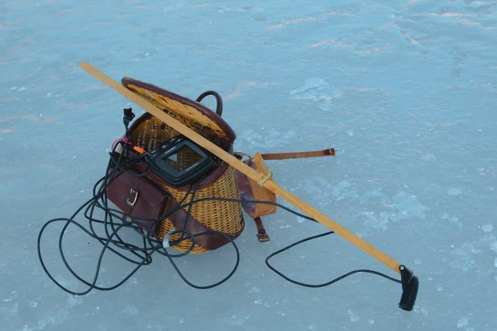 Brown bag on frozen lake with equipment and best ice fishing flasher