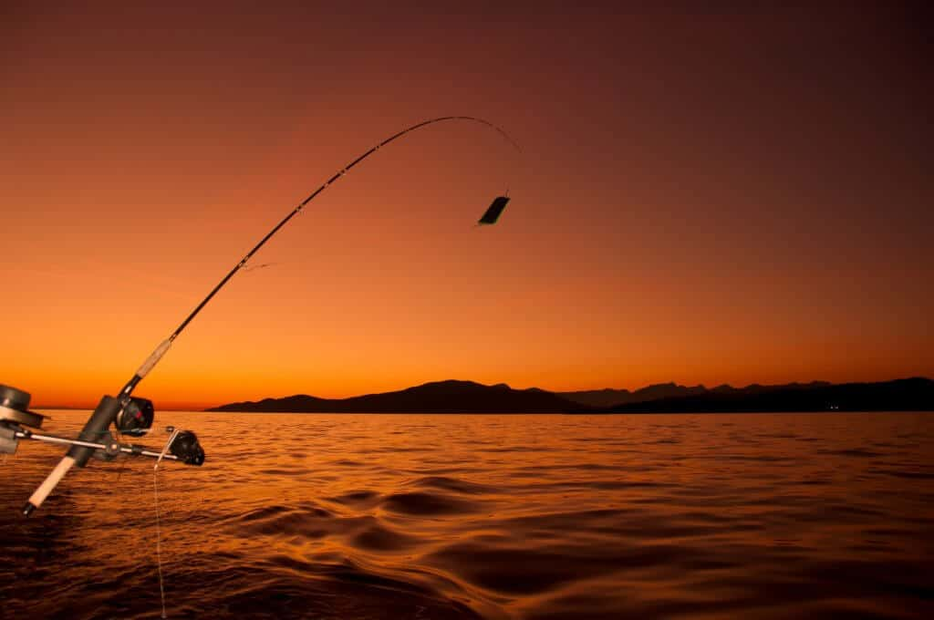 ocean fishing from boat at golden hour with a fishing rod in one of the best crappie rod holders