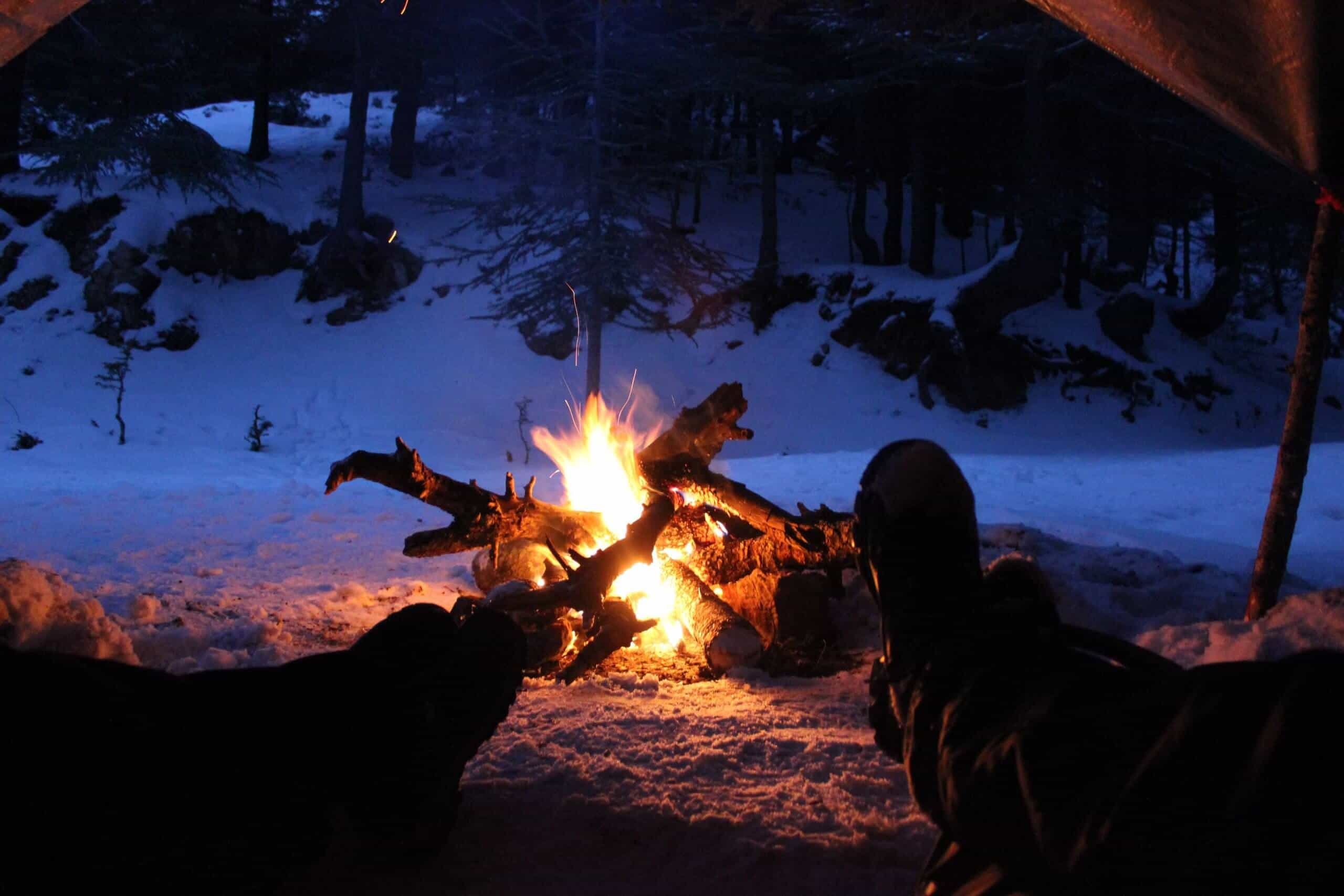 two people lying in a tent wearing the best thermal underwear for extreme cold warming their feet at a fire in the snow