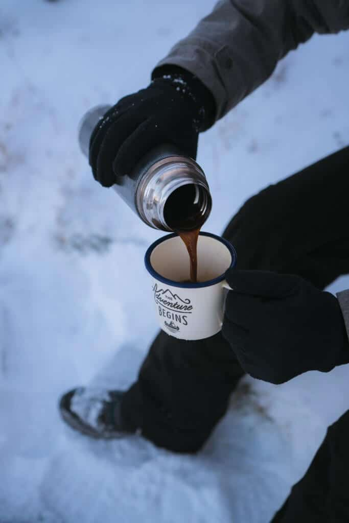 man pouring coffee in a mug while sitting in the snow wearing ice fishing gloves