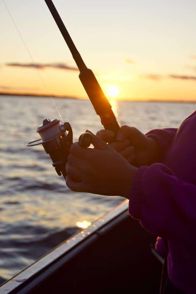 Person fishing from a boat with a sunset in the background using one of the best conventional reel for bottom fishing