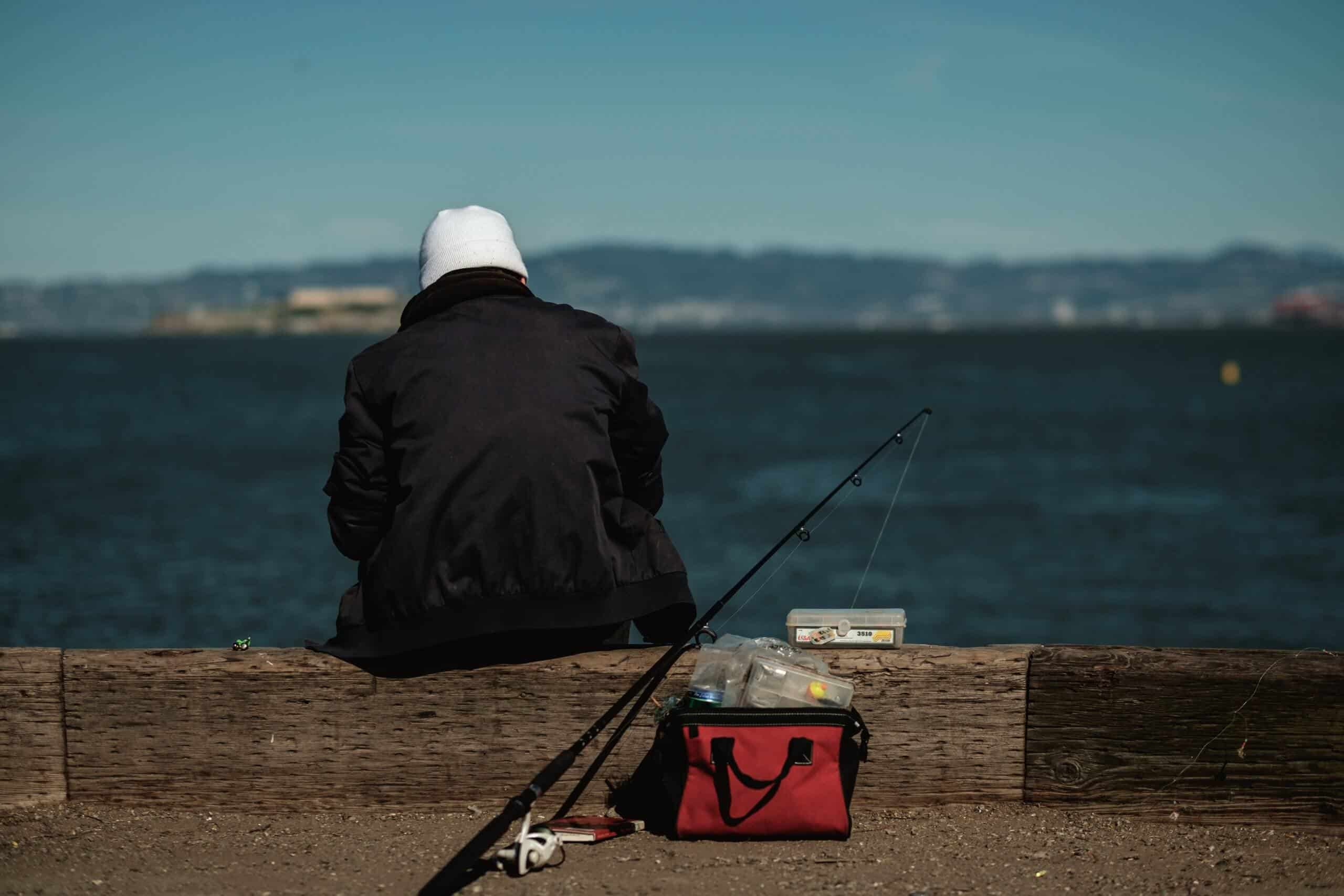 Man in black jacket sitting at a dock with a fishing rod and its best line for crappie in the water