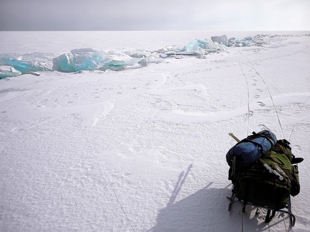A backpack on a sled in the ice