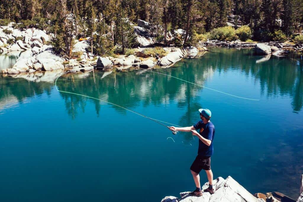 Man standing on rocks fly fishing in a lake