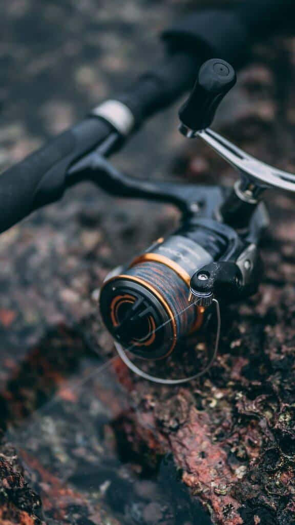 one of the best microspinning reel in black lying on the ground