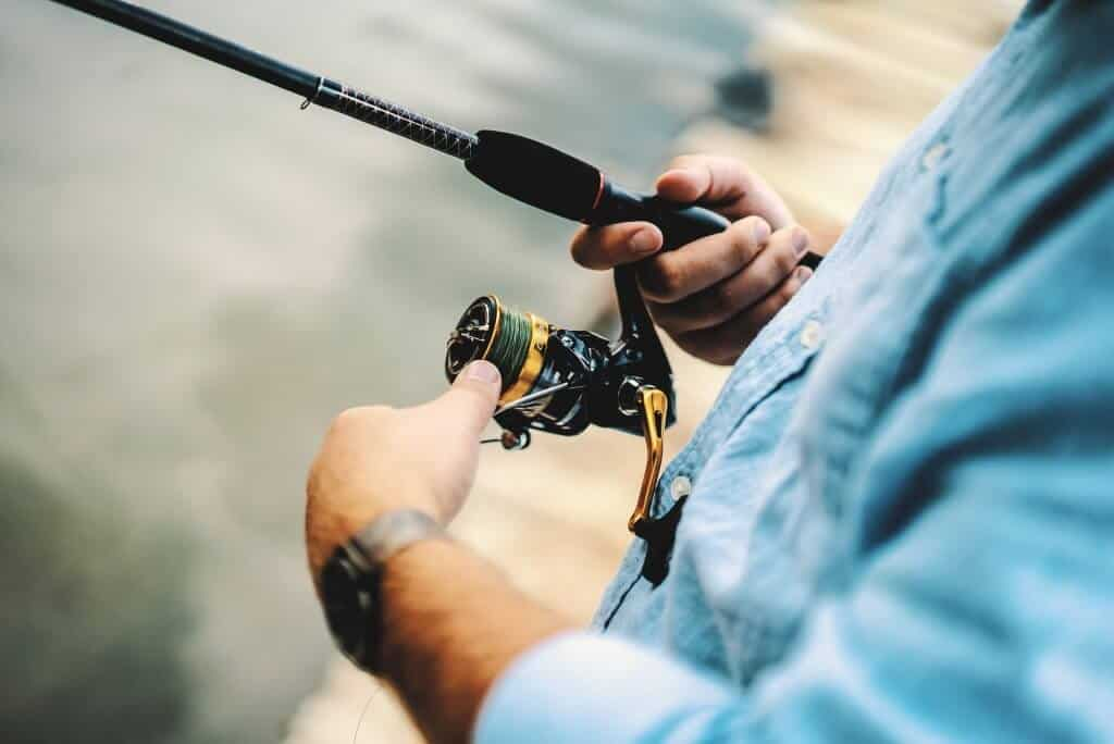 Man in blue shirt using one of the best spinning reel under 50$ in gold