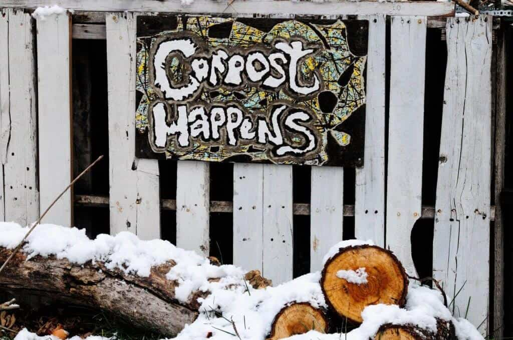 """Can fishing worms be used for composting? Sign saying """"compost happens"""" hanging on a fence in the winter"""