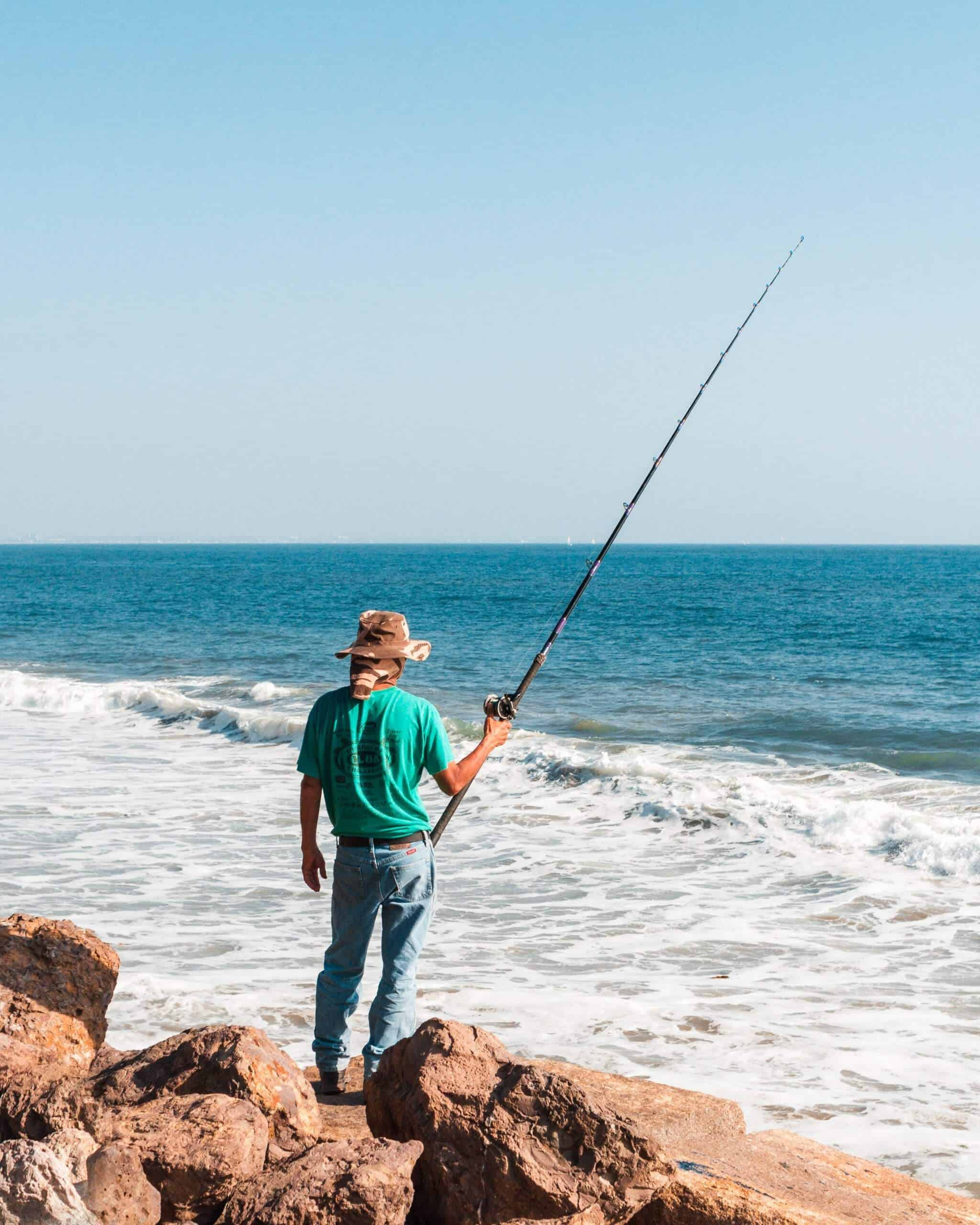 Man standing on rocks holding one of the best baitcasting rod under $100 in the ocean