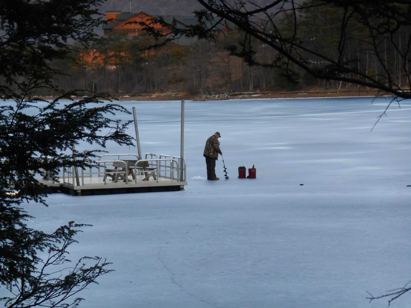 Man standing on a frozen lake using one of the best battery powered ice augers