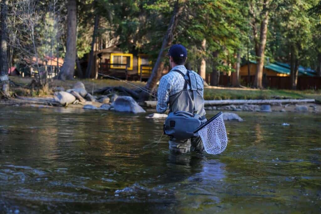 Man wearing some of the best fly-fishing waders for the money fishing in a stream