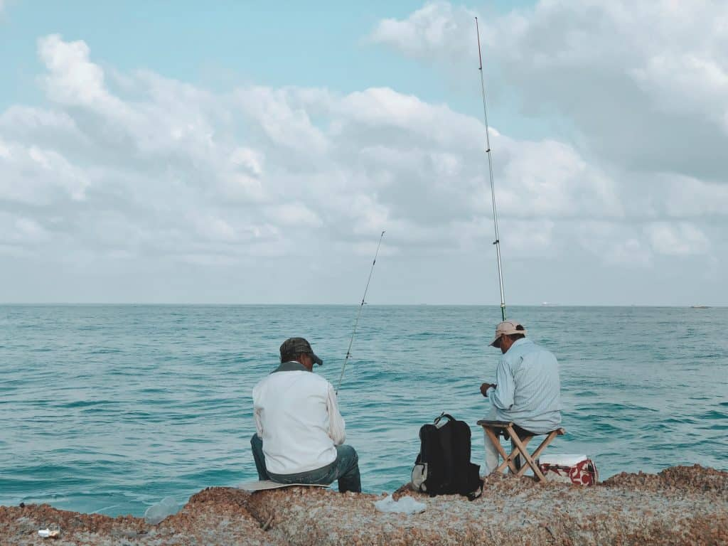 Fishing requires patience: two men sitting on rocks in front of the ocean holding rods waiting for fish to bite