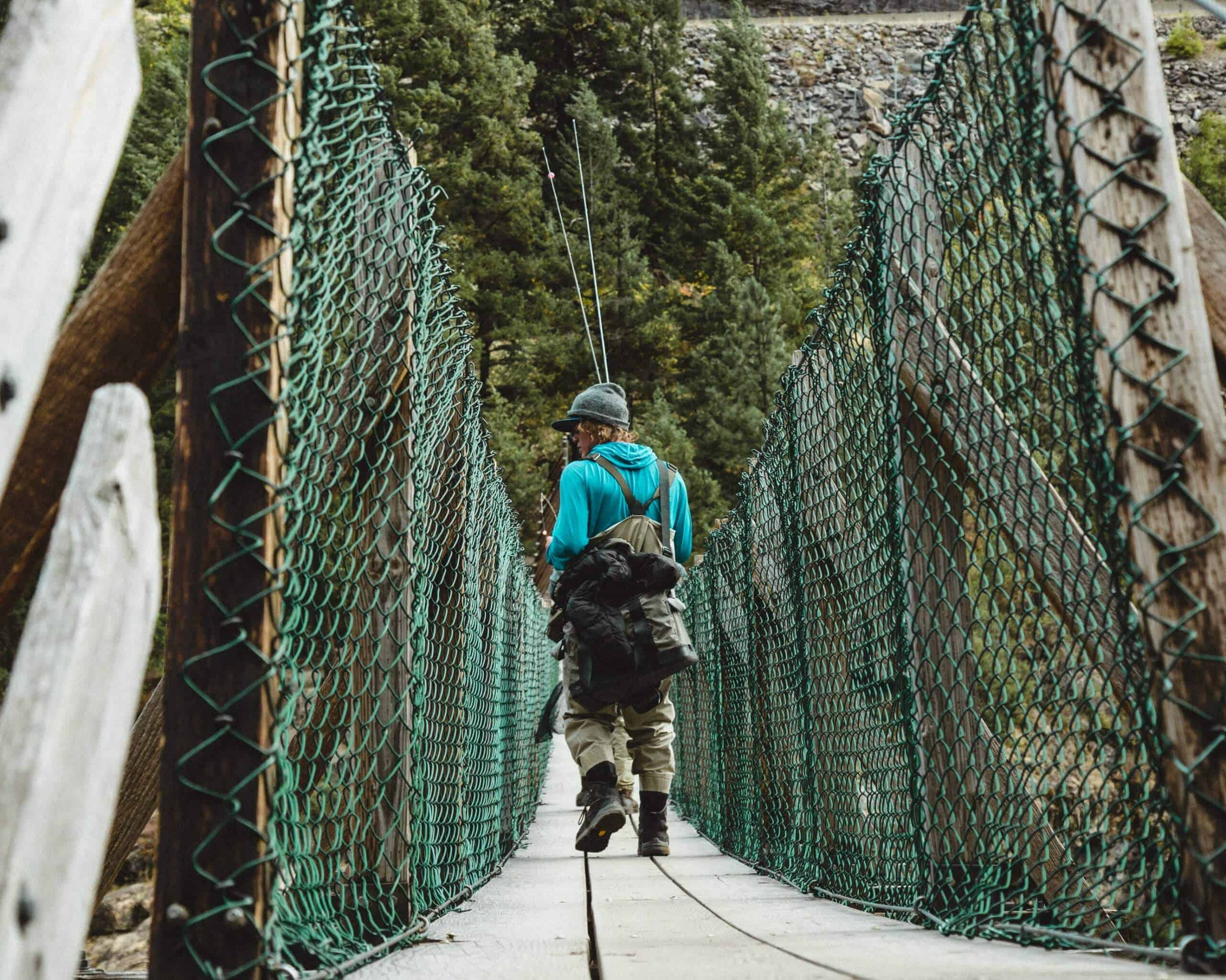 Man wearing one of the best fishing backpack walking on a bridge
