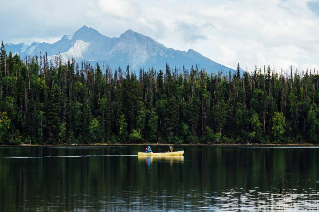 Two fishermen on a lake sitting in one of the best tandem fishing kayaks on their way a fishing spot