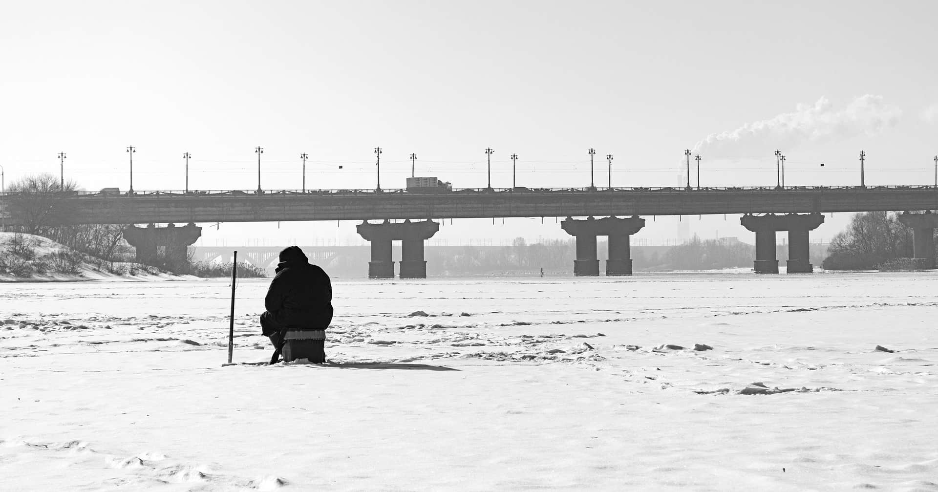 Person sitting in frozen river wearing one of the best ice fishing bibs available