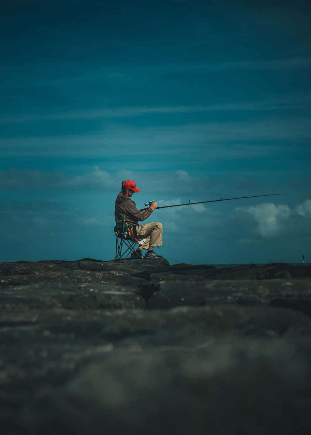 Fishing man sitting on a peer on one of the best portable fishing chairs