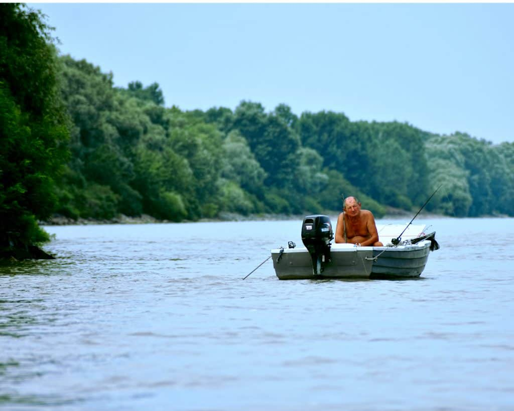man on a boat on a lake fishing using one of the best finder for small boats