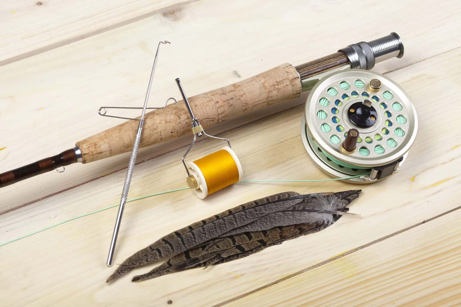 One of the best 5 weight fly rods on a wooden surface with feathers next to it