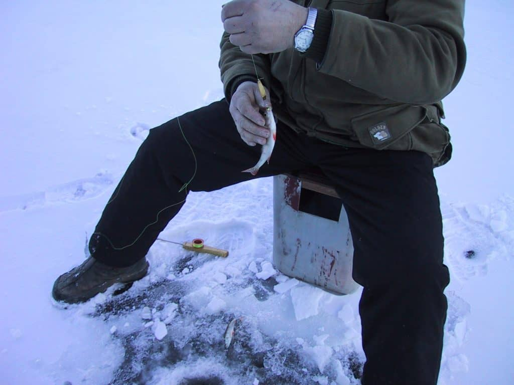 Man wearing some of the best ice fishing boots reeling in a catch from a drilled hole on a frozen lake