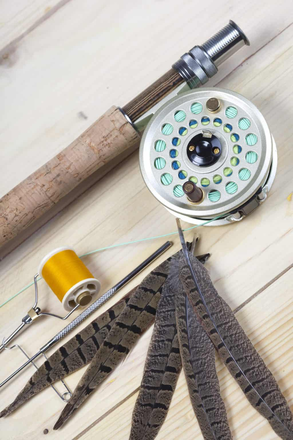 a fly fishing rod and reel lying on a wooden surface. also some feathers. Will fishing line melt or burn?