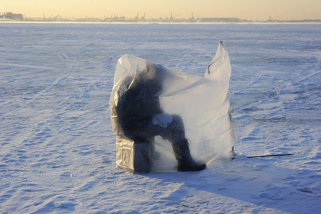 A man practicing sport fishing on the ice sitting covered under plastic