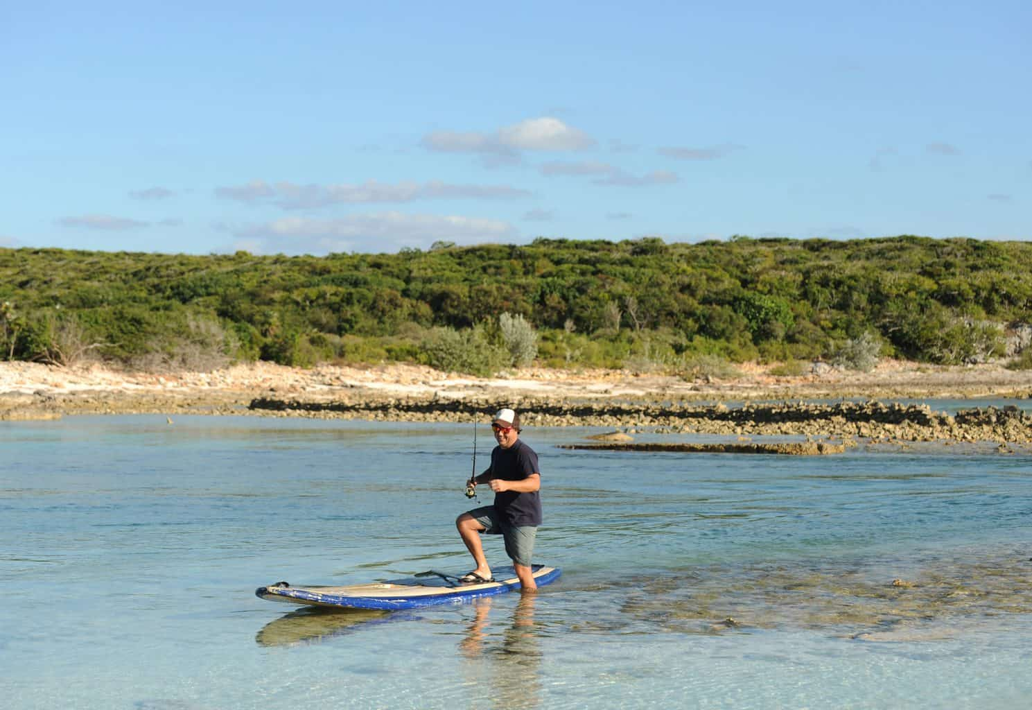 Man stepping off one of the best fishing paddle boards while fishing in scenic tropical destination