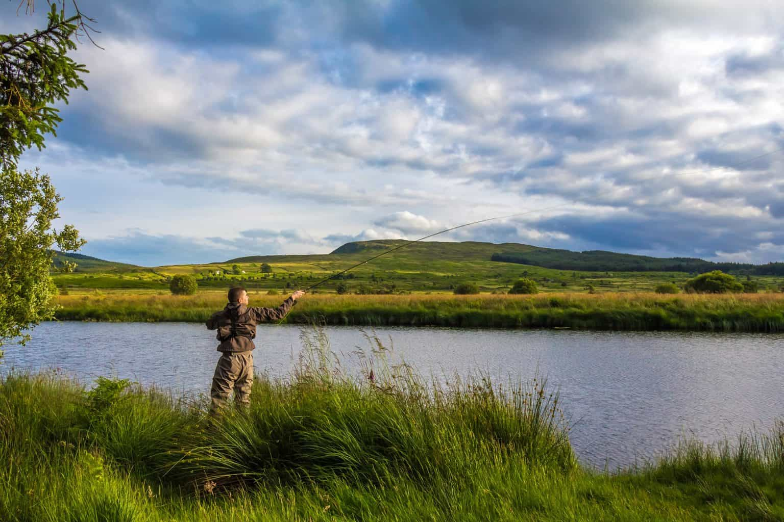 A fisherman fly fishing for crappie in the evening sun on the Blackwater of Dee, Galloway, Scotland