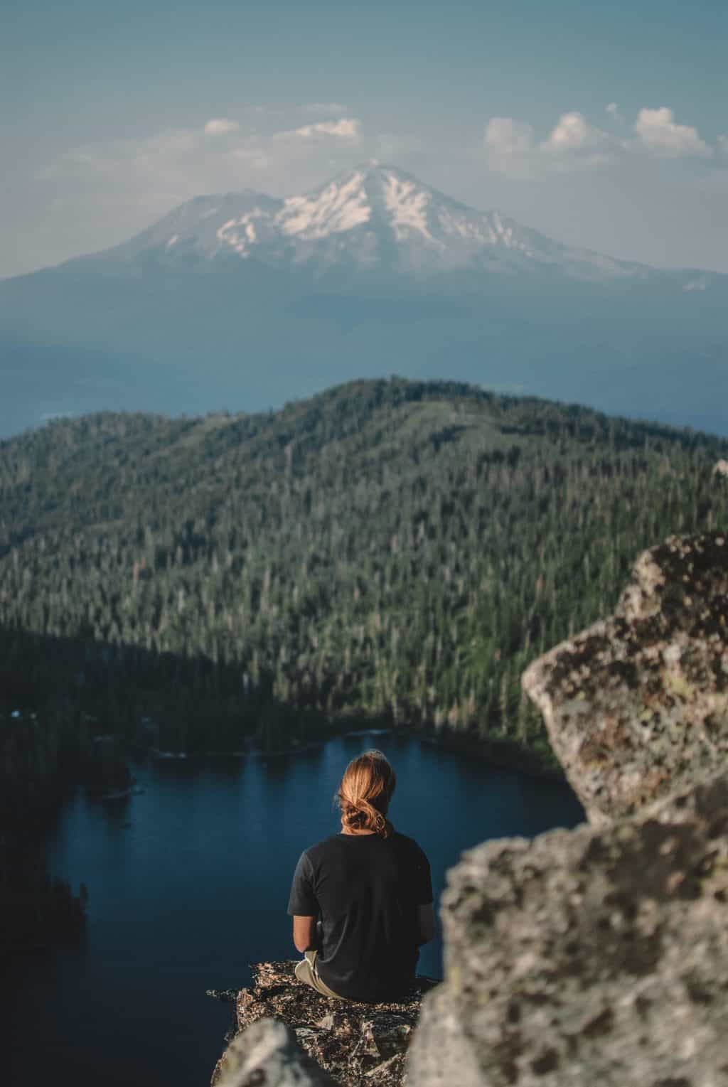 A woman sitting on a mountain overlooking a lake where there is great fly fishing in redding