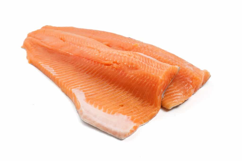 two salmon trout fillets over white background