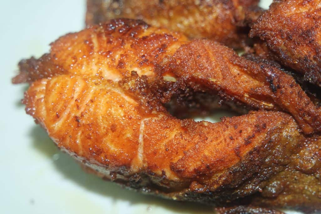 Spicy and crunchy barbecue of fried fish fillet on a white background. Homemade grilled trout fish steaks