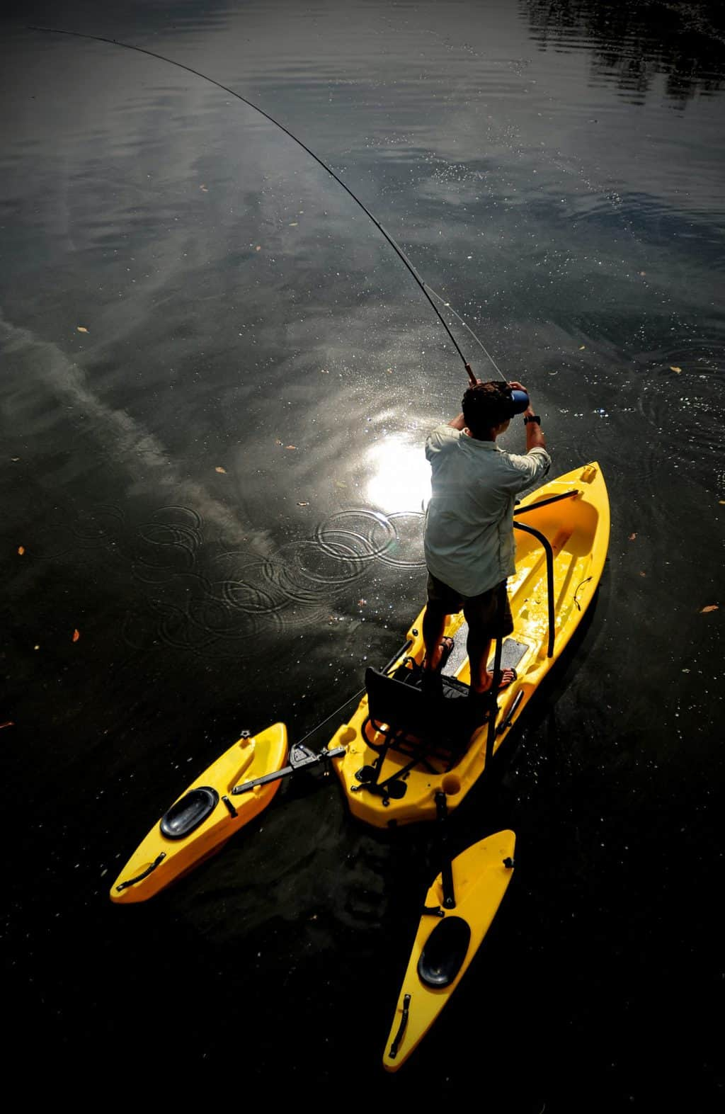 Man with brown hair fly fishing in a lake in one of the best fishing kayak under 600