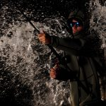 main testing out one of the best rain jacket for fishing, holding fishing rod