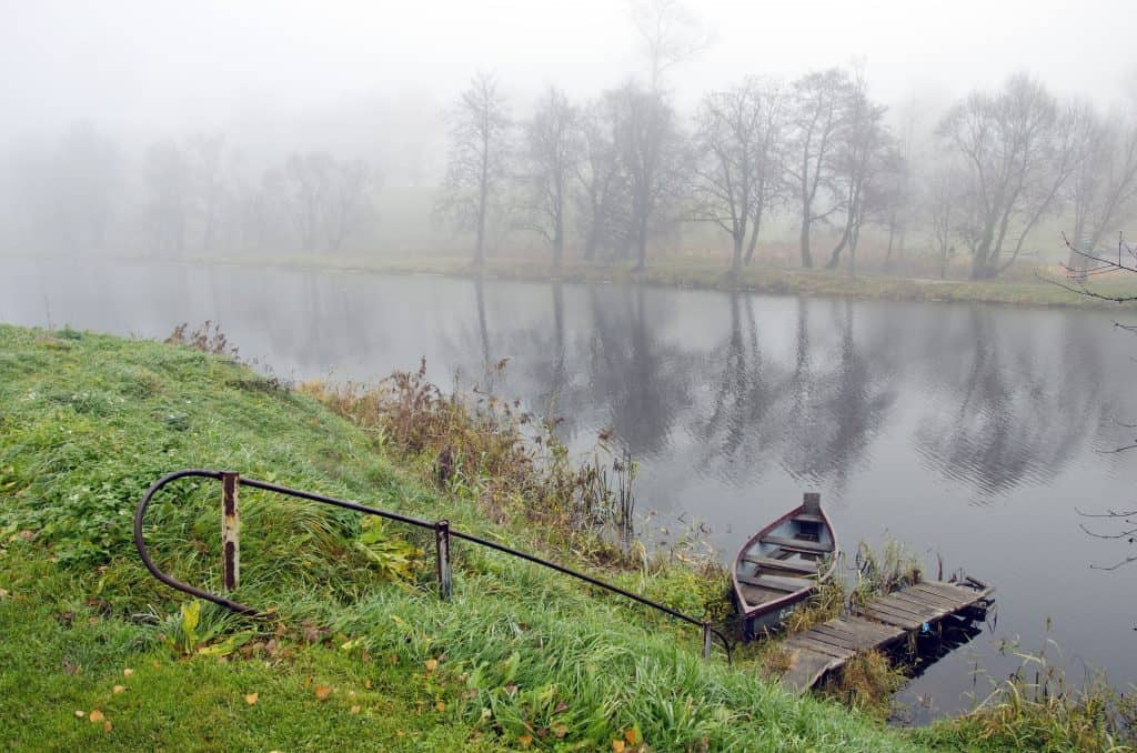 autumn time mist and boat in rural river