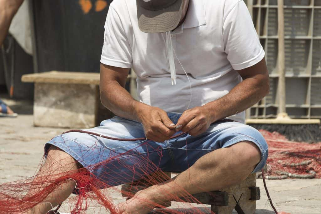 Fisherman repairs his net in Gallipoli (Le) in Souther Italy