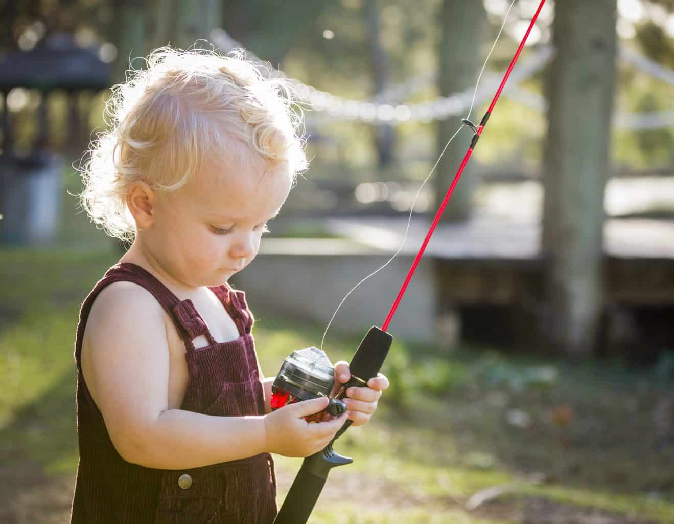 Cute Young Boy With Fishing Pole Outside at The Lake. Fishing with toddlers is fun!